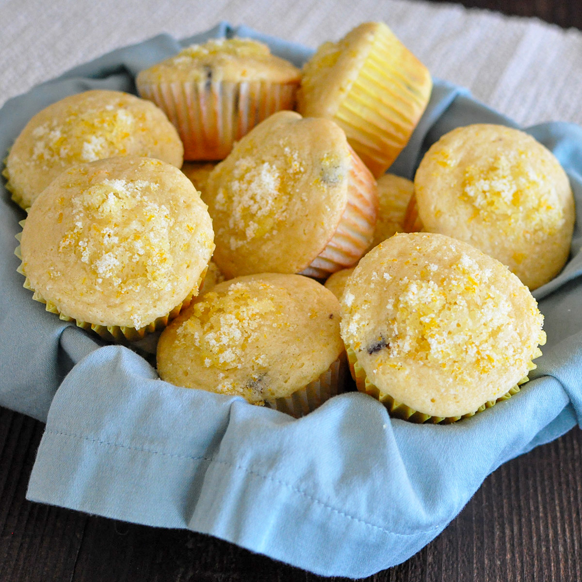 orange muffins in a basket lined with a blue napkin
