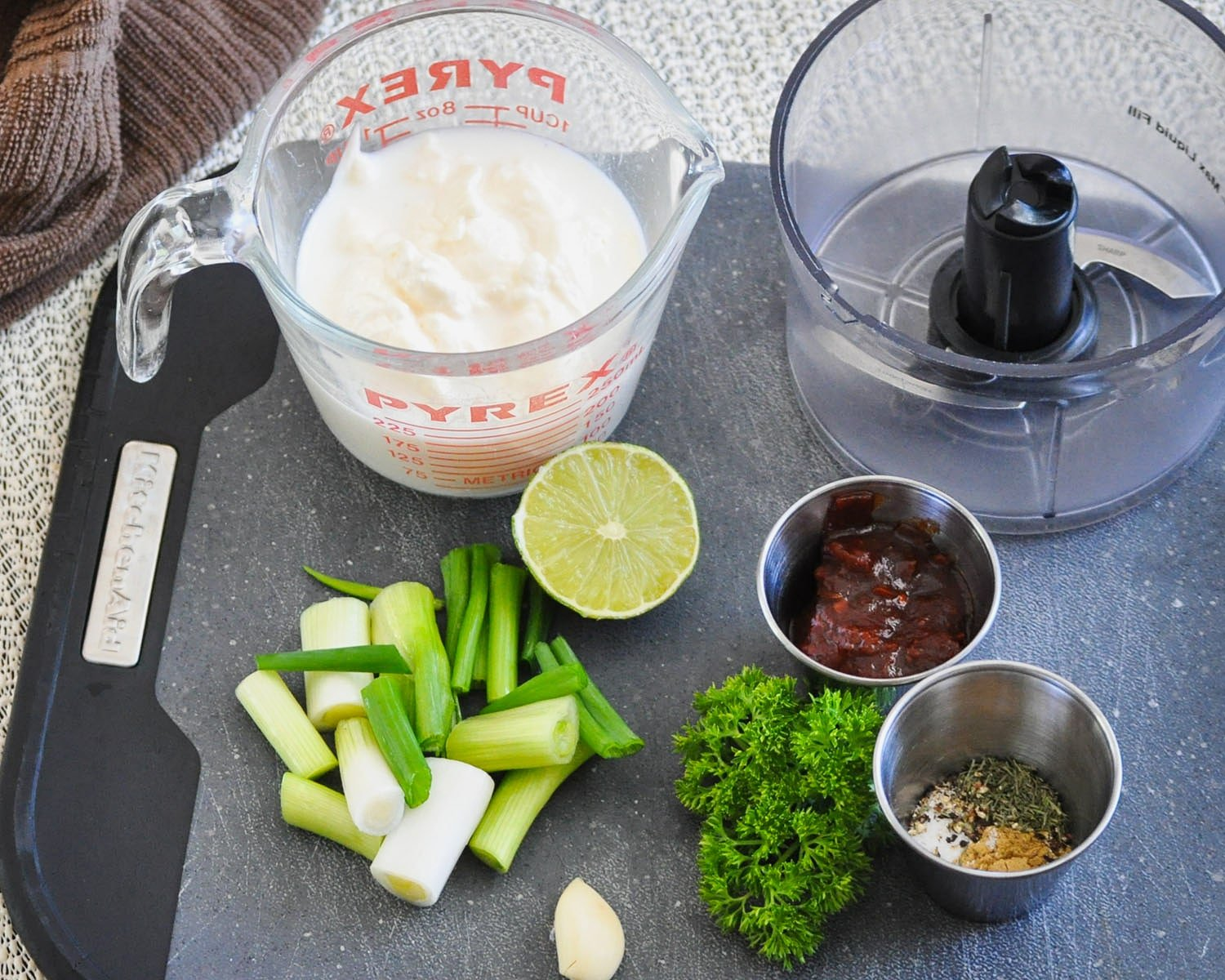 milk, mayo, green onion, garlic, spices, chipotle in adobo sauce, lime on a black cutting board