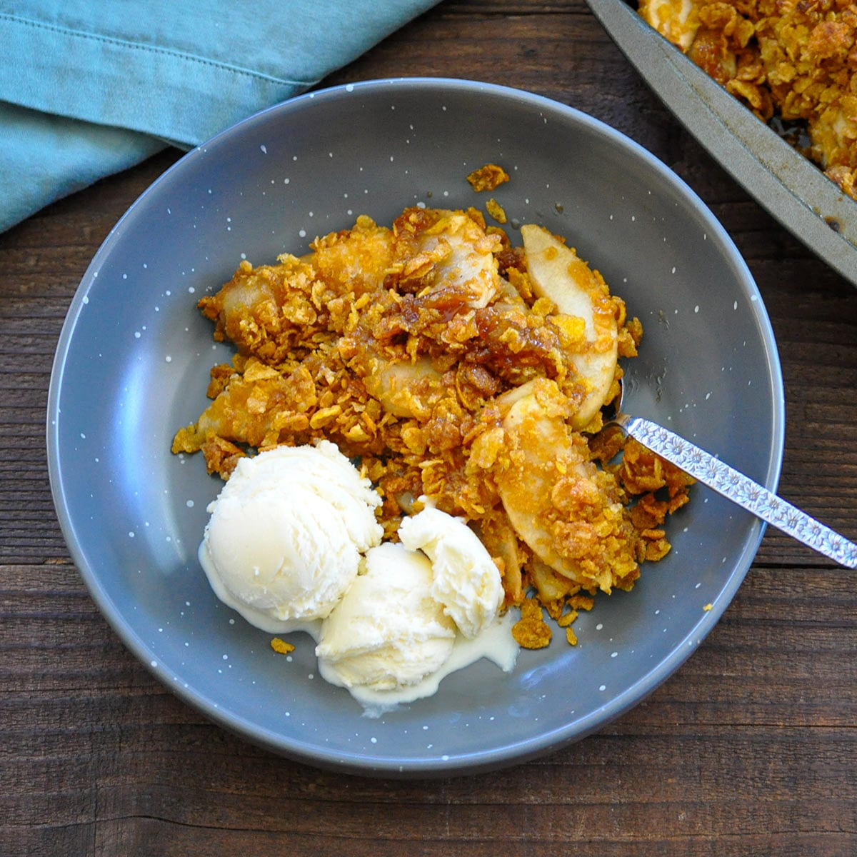 a bowl of apple crisp made with corn flakes and a side of vanilla ice cream