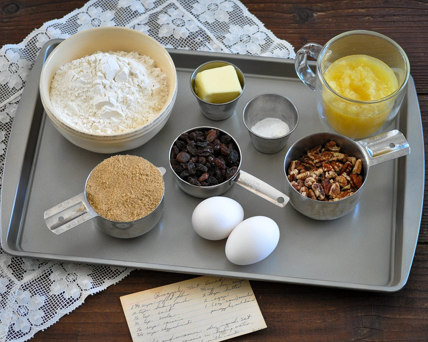 measured lour, raisins, brown sugar, butter, pineapple, nuts, eggs on a cookie sheet next to a recipe card