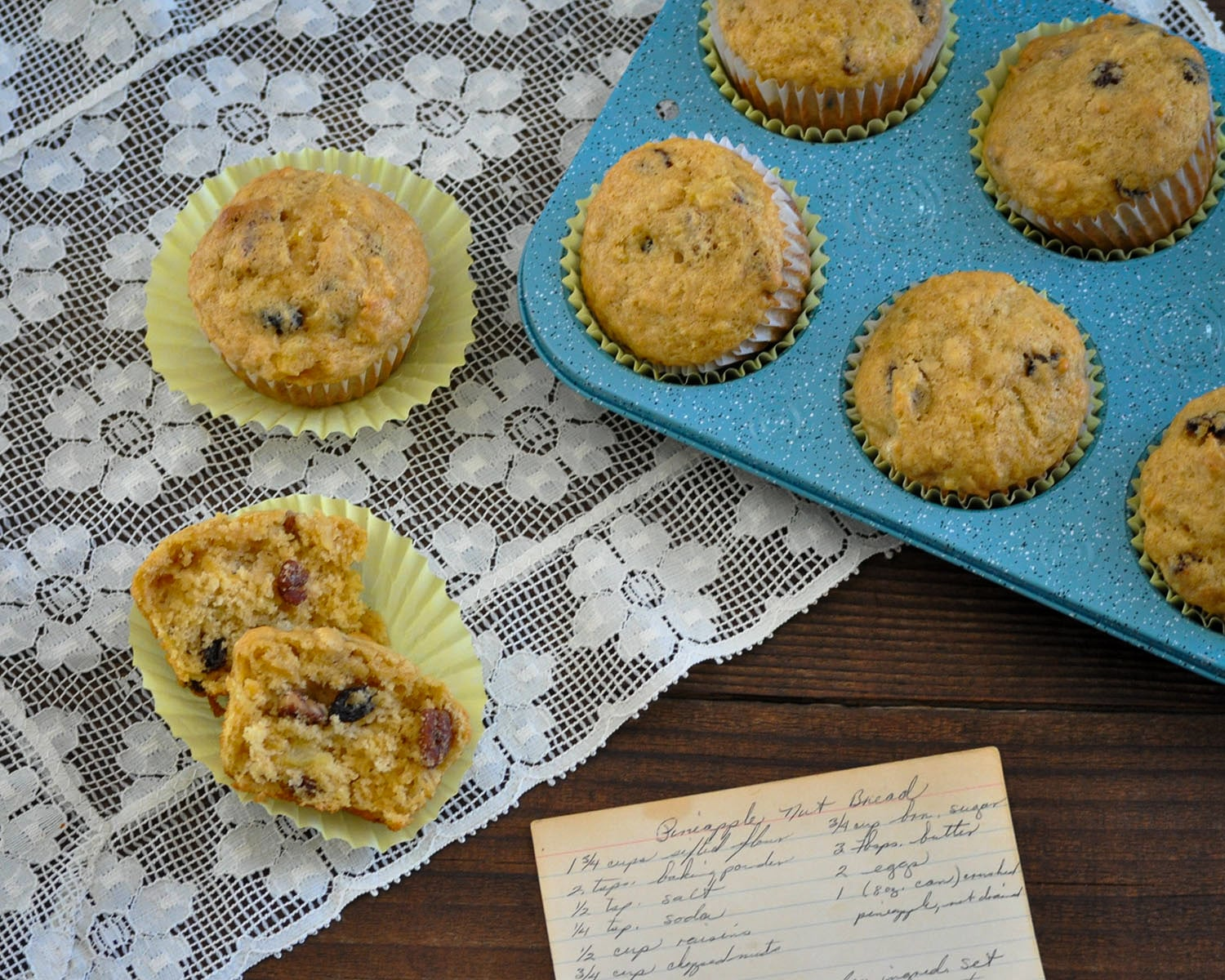 Just baked pineapple muffins on a doilie and a blue muffin tin next to an old recipe card.