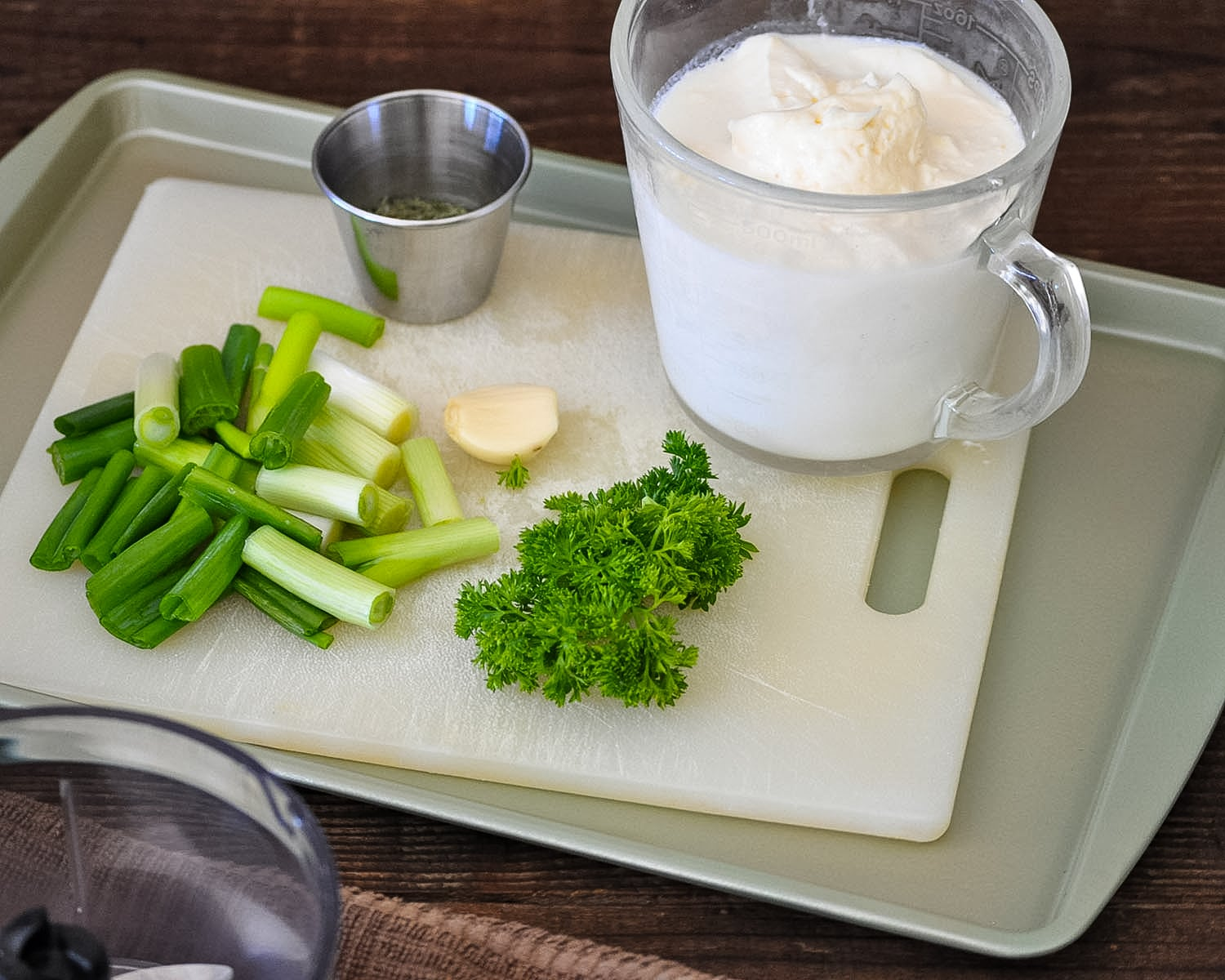 chopped green onions and fresh parsley on a white cutting board next to a measuring cup of mayo and milk
