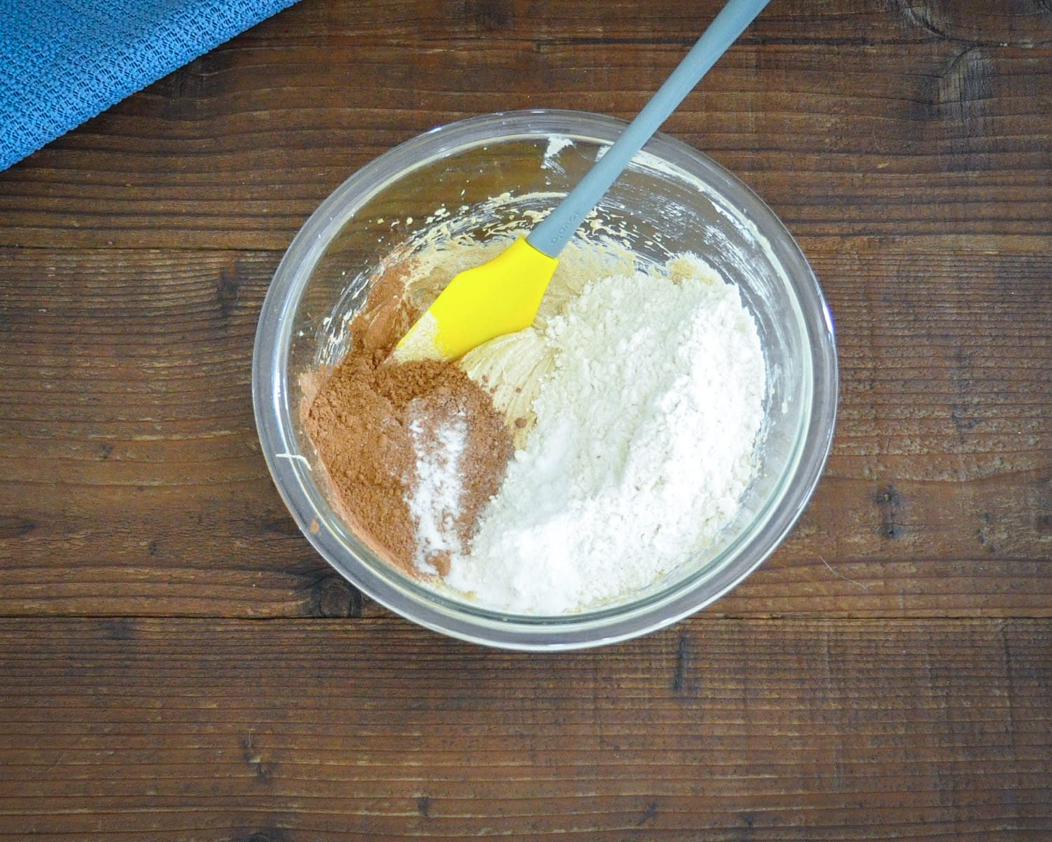 flour, cocoa powder, salt and baking soda added to a creamed mixture of butter, sugar, egg and vanilla in a glass bowl. ready to be stirred with a rubber spatula.