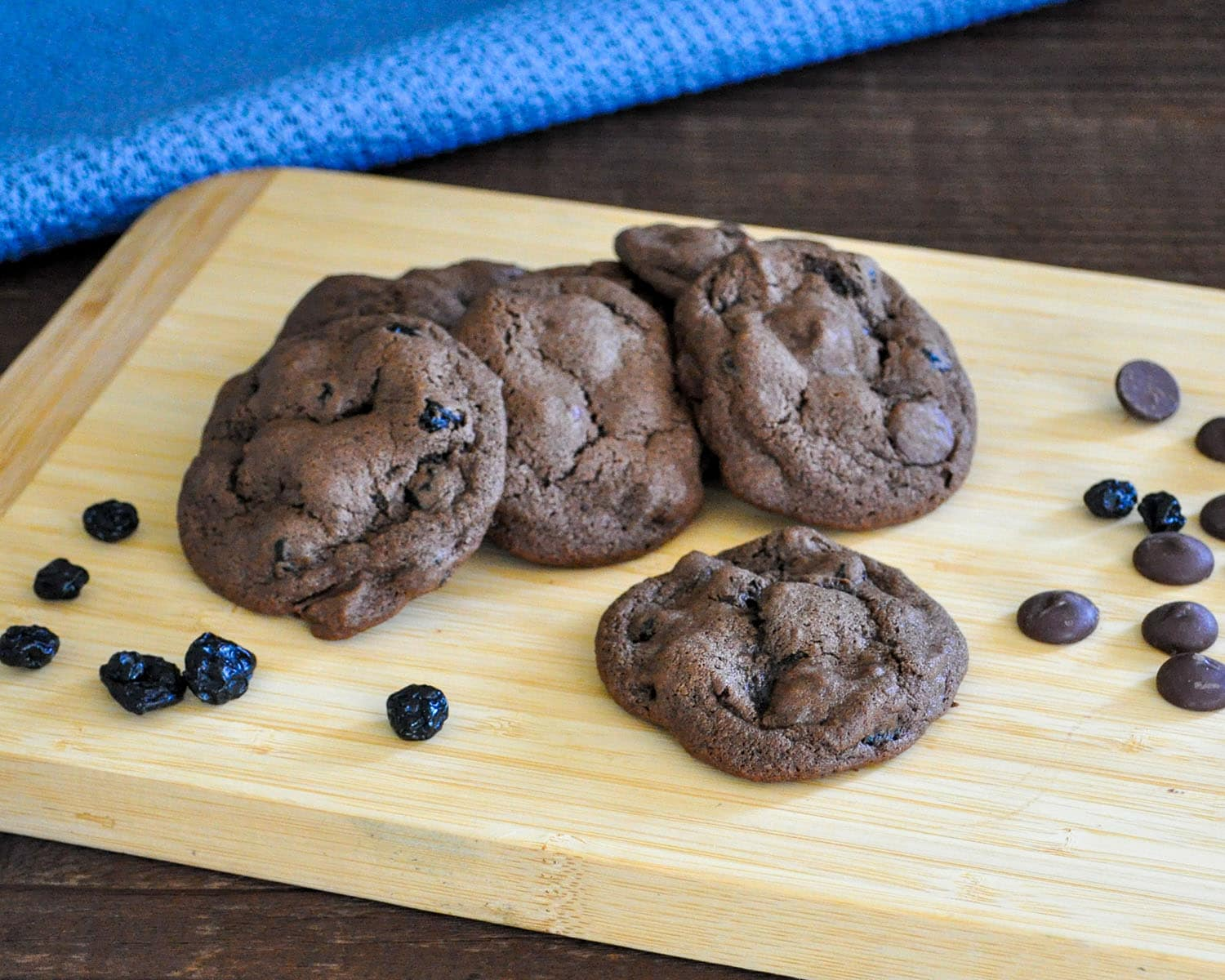 a pile of chocolate cookies filled with dried blueberries and chocolate chips on a bamboo board