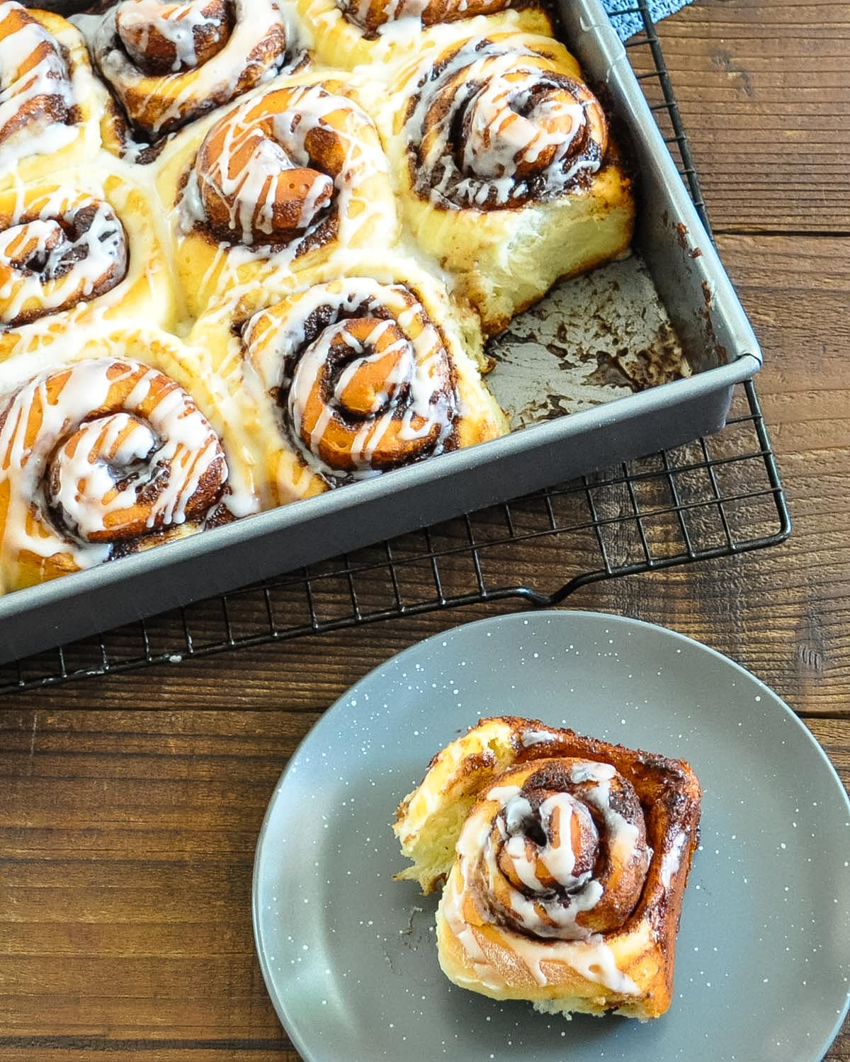 glazed chocolate cinnamon rolls on a plate and in a pan