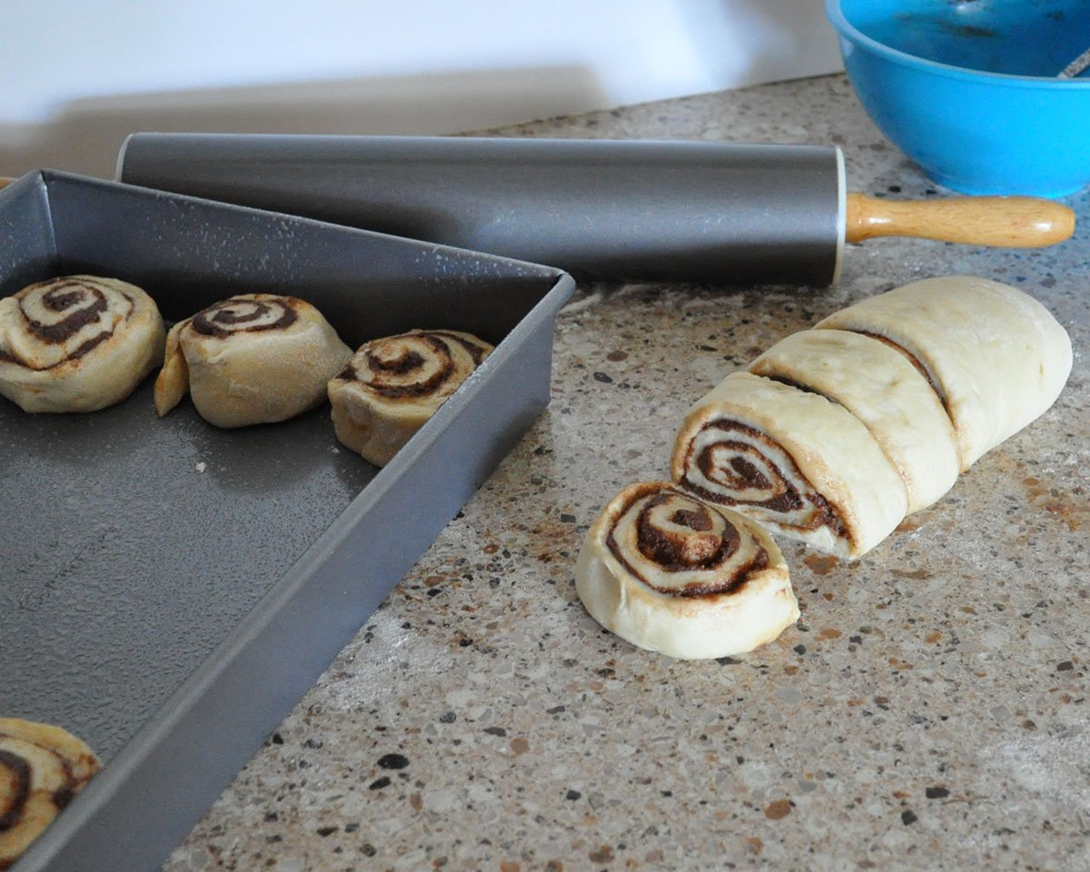 cinnamon rolls being sliced and put into a silver pan next to a rolling pin