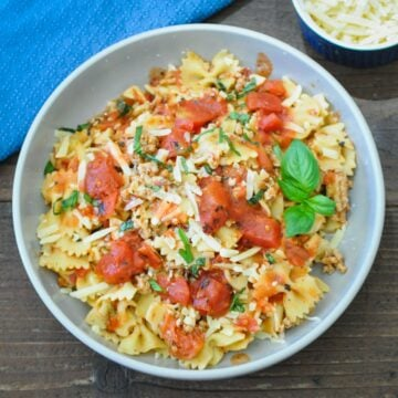 pasta, ground turkey, tomatoes in a gray bowl topped with basil and parmesan cheese