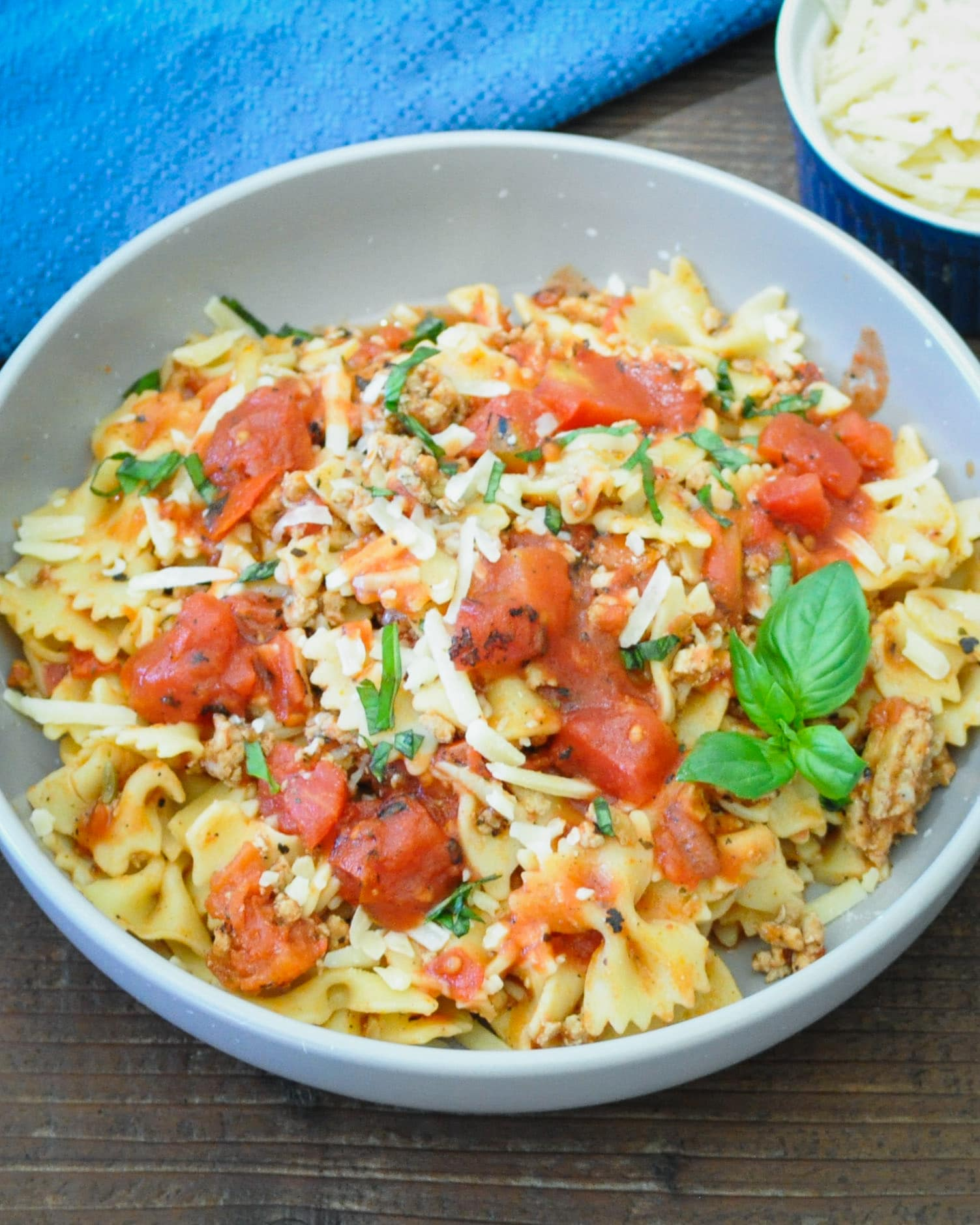 ground turkey, pasta with tomatoes in a gray bowl