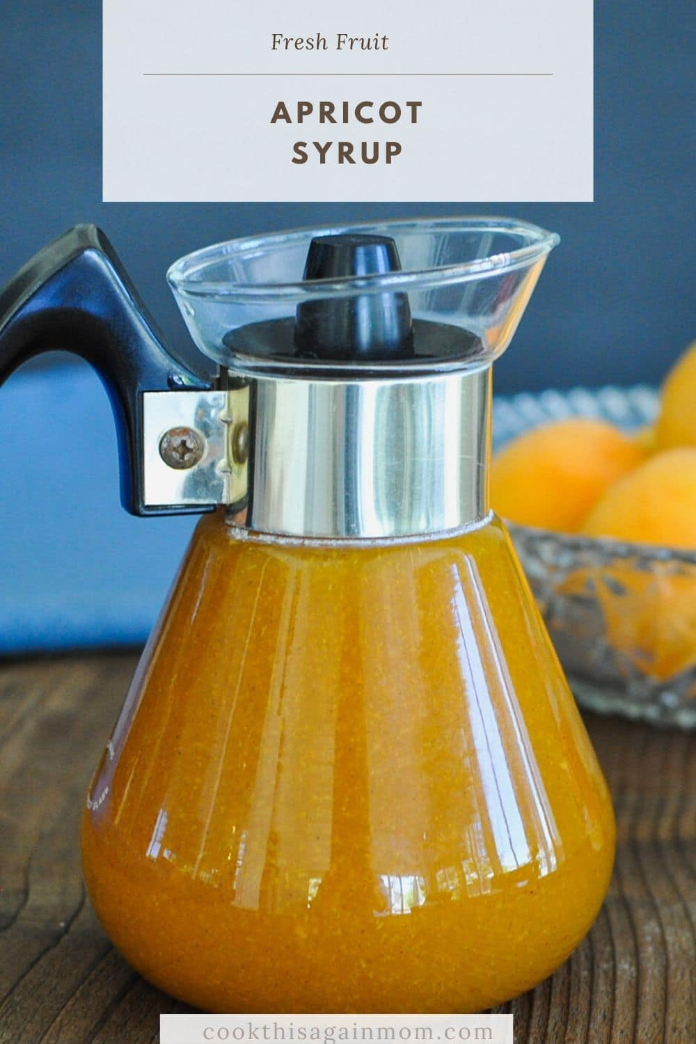 A close up photo of a glass syrup dispenser filled with homemade fruit syrup