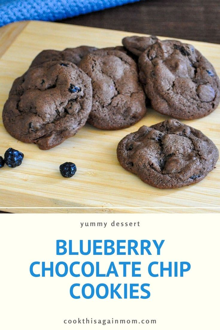 a stack of blueberry chocolate cookies sitting on a bamboo cutting board