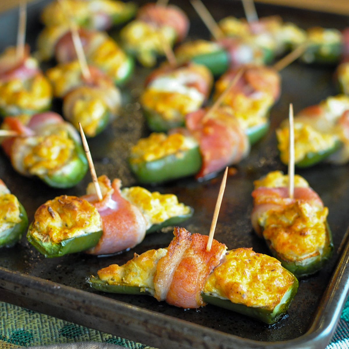 a baking sheet filled with bacon wrapped stuffed jalapenos