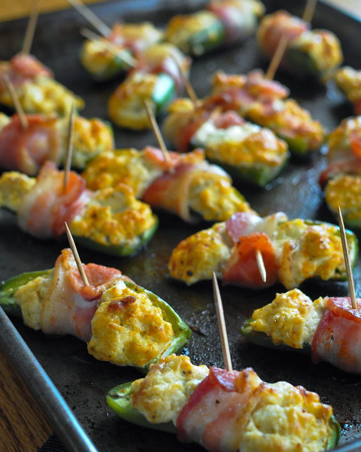 a baking sheet with bacon wrapped stuffed jalapeno appetizers
