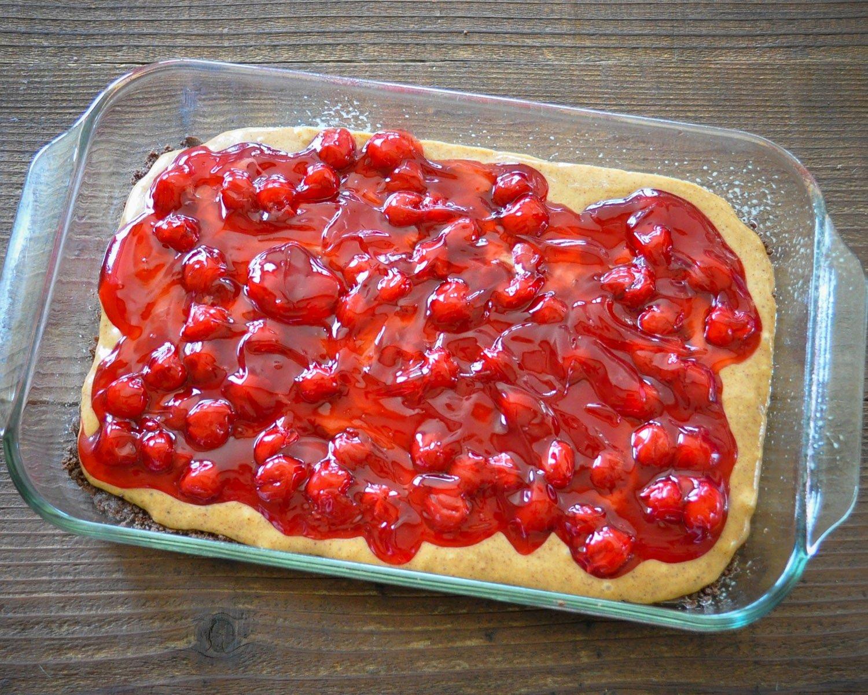 cherry pie filling over an almond batter on a chocolate dessert bar base