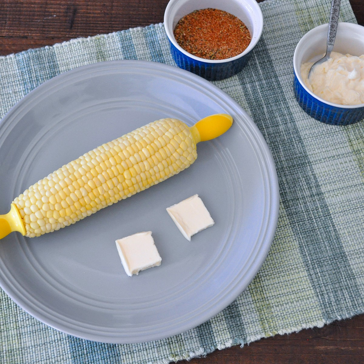 corn and butter on a gray plate