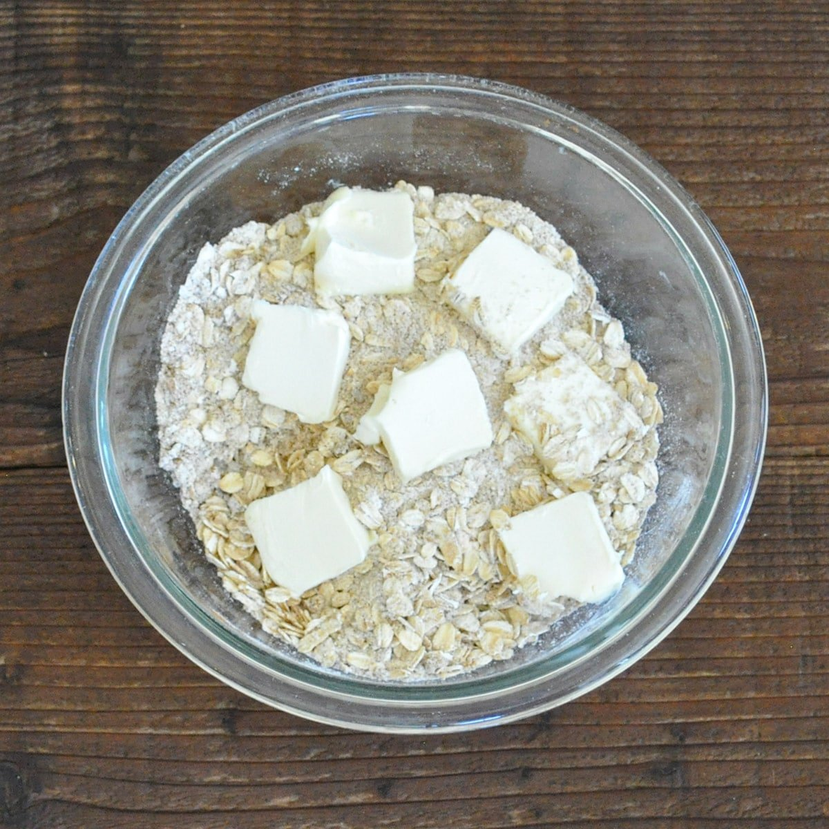 brown sugar, flour and oats in a glass bowl topped with chunks of butter