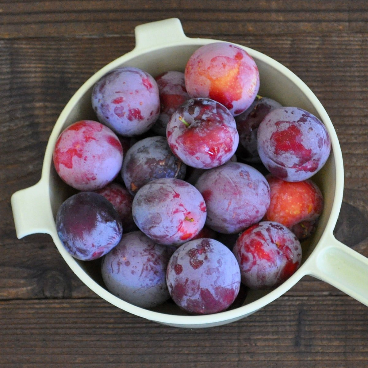 a strainer full of fresh plums