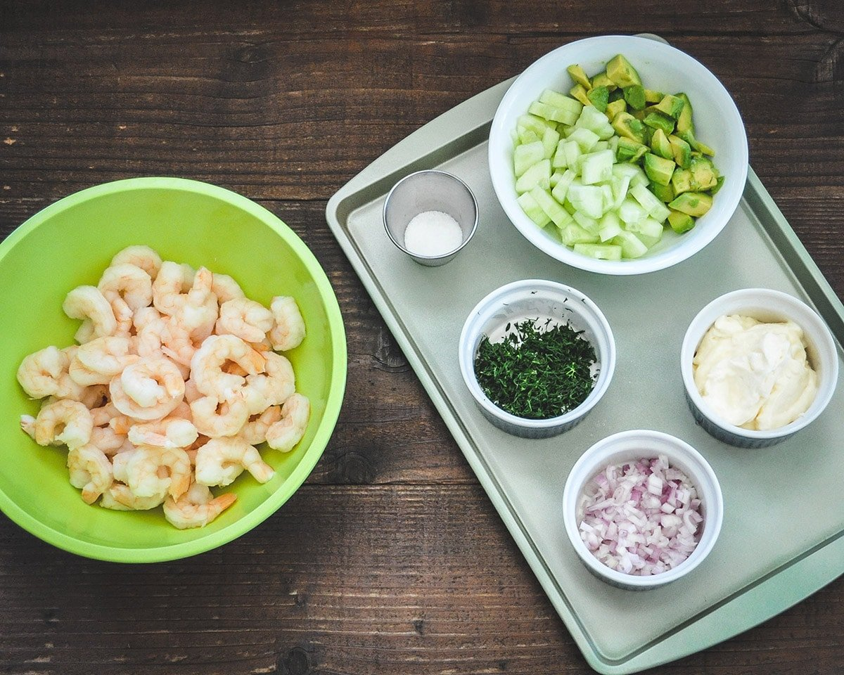Over head picture of cooked shrimp, avocado, cucumber, chopped shallot, fresh dill and salt for shrimp salad