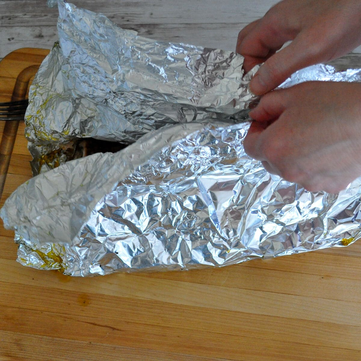 opening a foil packet of fish that has just been removed from bbq