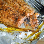 a close up photo a grilled salmon in foil next to a fork