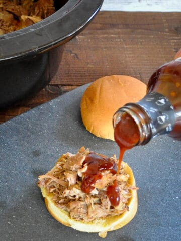 shredded pork on a bun with bbq sauce being poured on top
