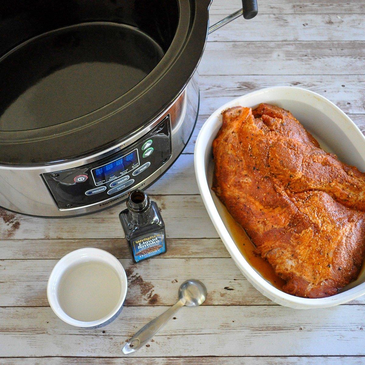 a crock pot, pork butt, and liquid smoke