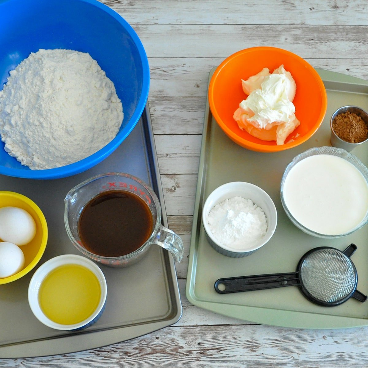 white cake mix in a blue bowl, eggs, oil, coffee, mascarpone, powdered sugar, and cream measured out for a recipe