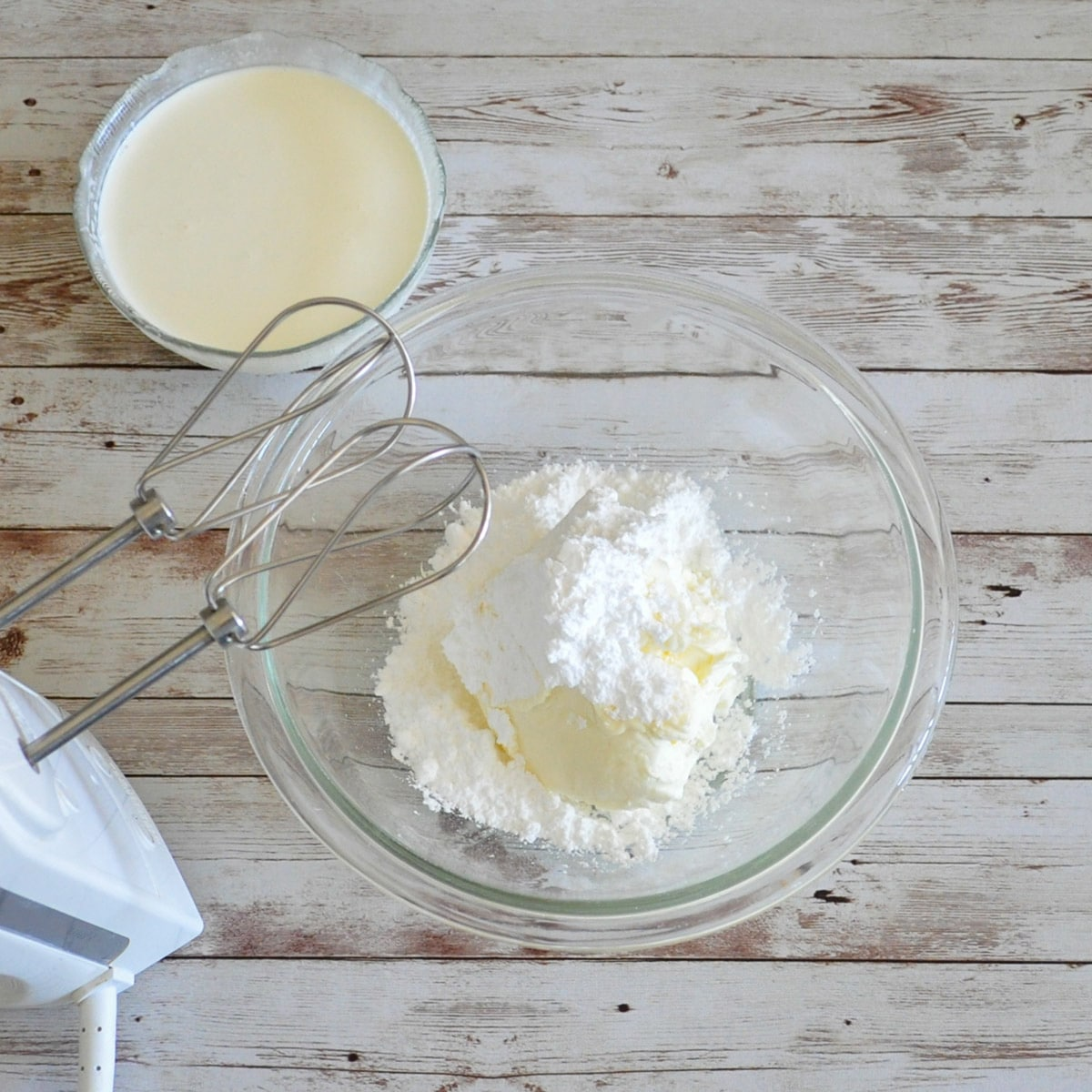 mascarpone with powdered sugar in a clear bowl with heavy cream and a mixer on the side
