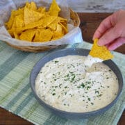 a bowl of tortillas next to a bowl of dip with someone dipping a chip