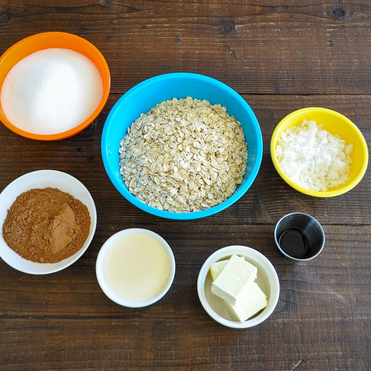 sugar, oats, coconut, cocoa powder, milk, butter, and vanilla in separate bowls measured out for a uncooked cookie recipe