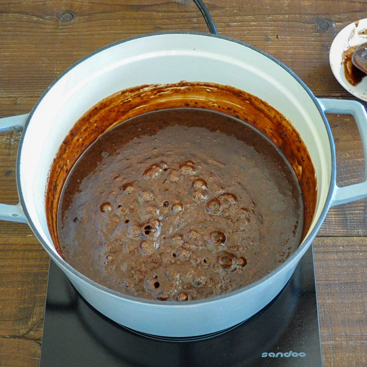 butter, milk, cocoa, and sugar that is coming to a boil in a large pan