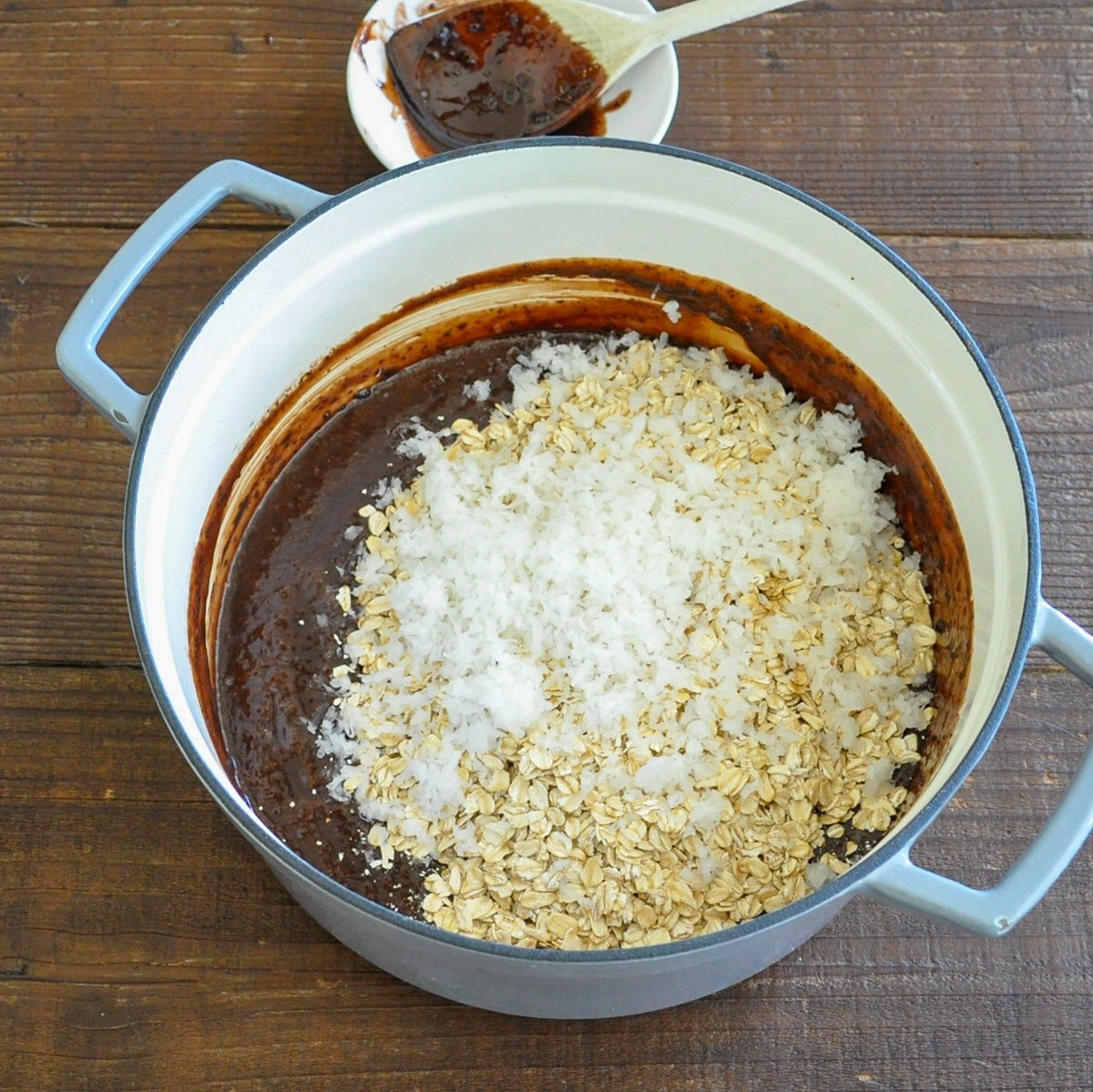 Oatmeal, coconut, and vanilla added to a cocoa, milk, butter and sugar cookie base in a large pan