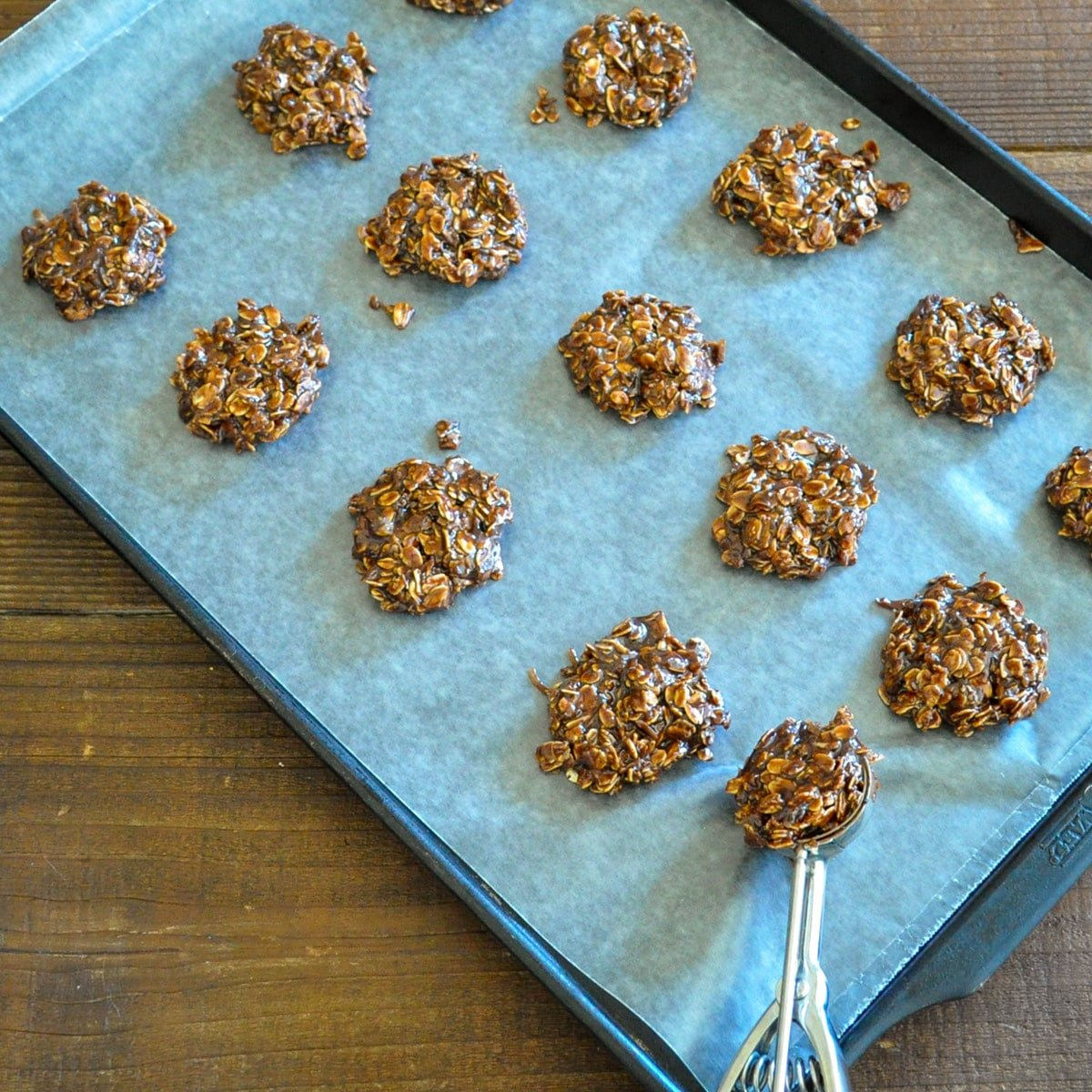 no-bake chocolate oatmeal cookies being placed on a wax paper covered cookie sheet
