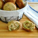a split open zucchini muffin next to a basket of muffins