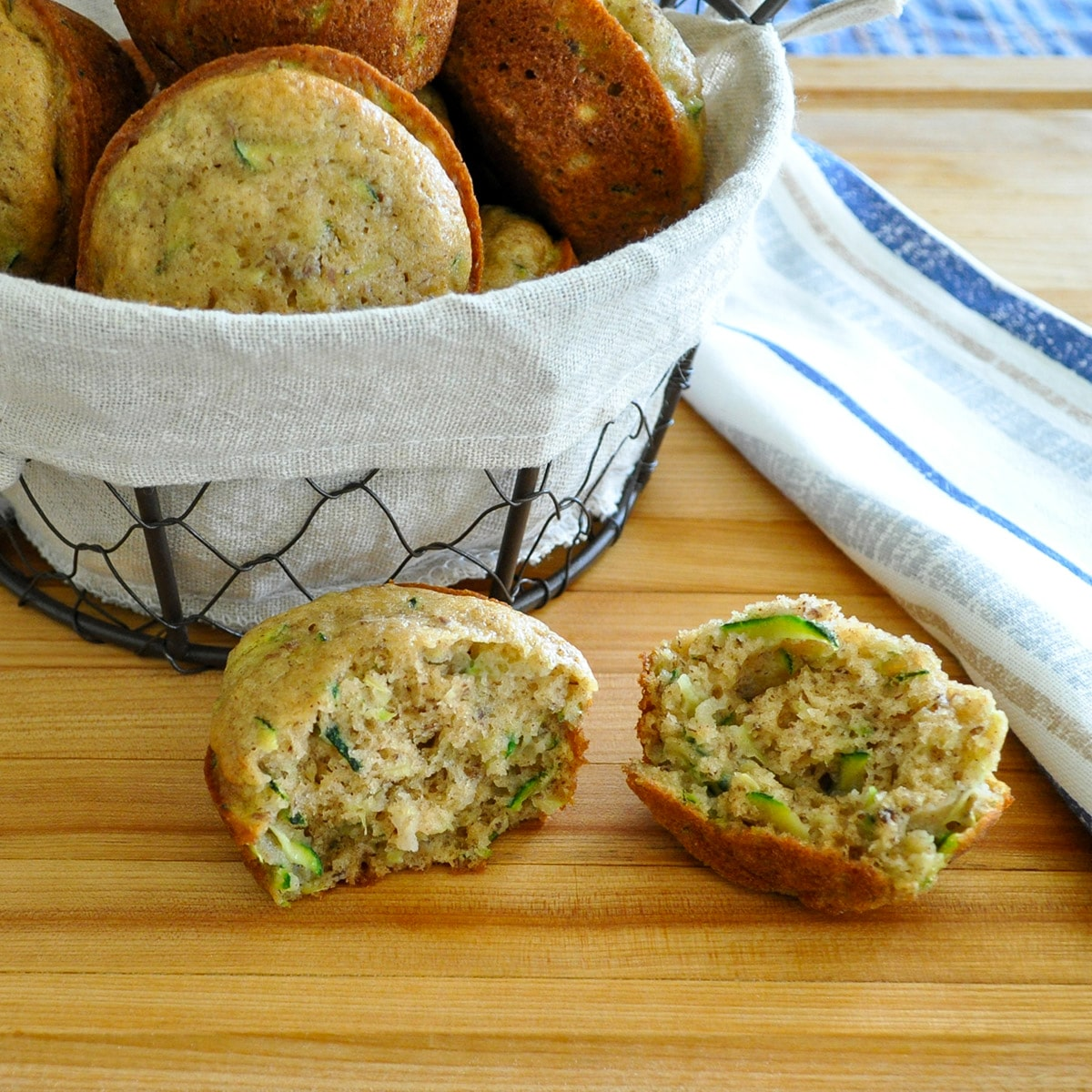 a split open zucchini muffin next to a basket of muffins