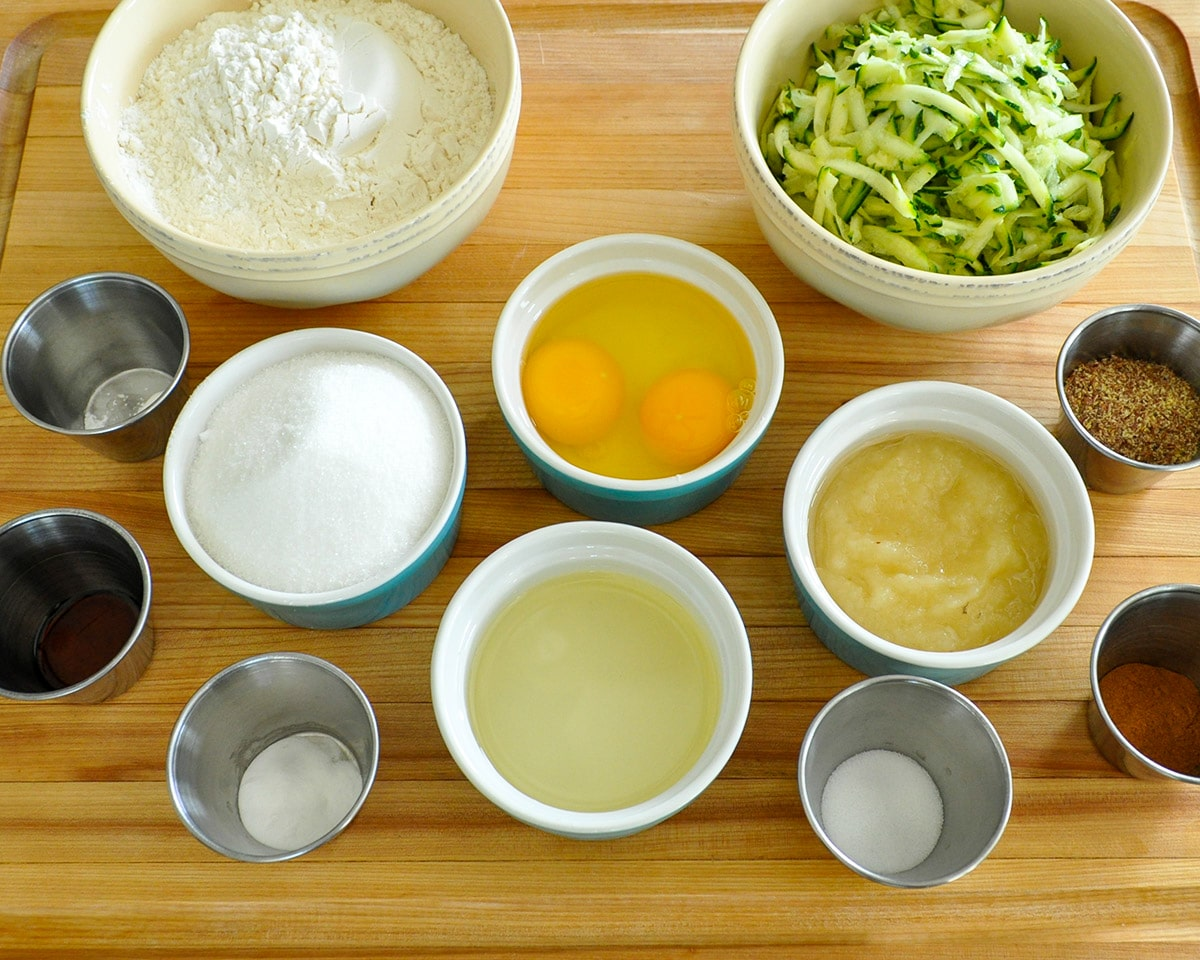 Measured out bowls of zucchini, flour, eggs, sugar, applesauce, oil, vanilla, salt, baking soda, baking powder, cinnamon, flax seed