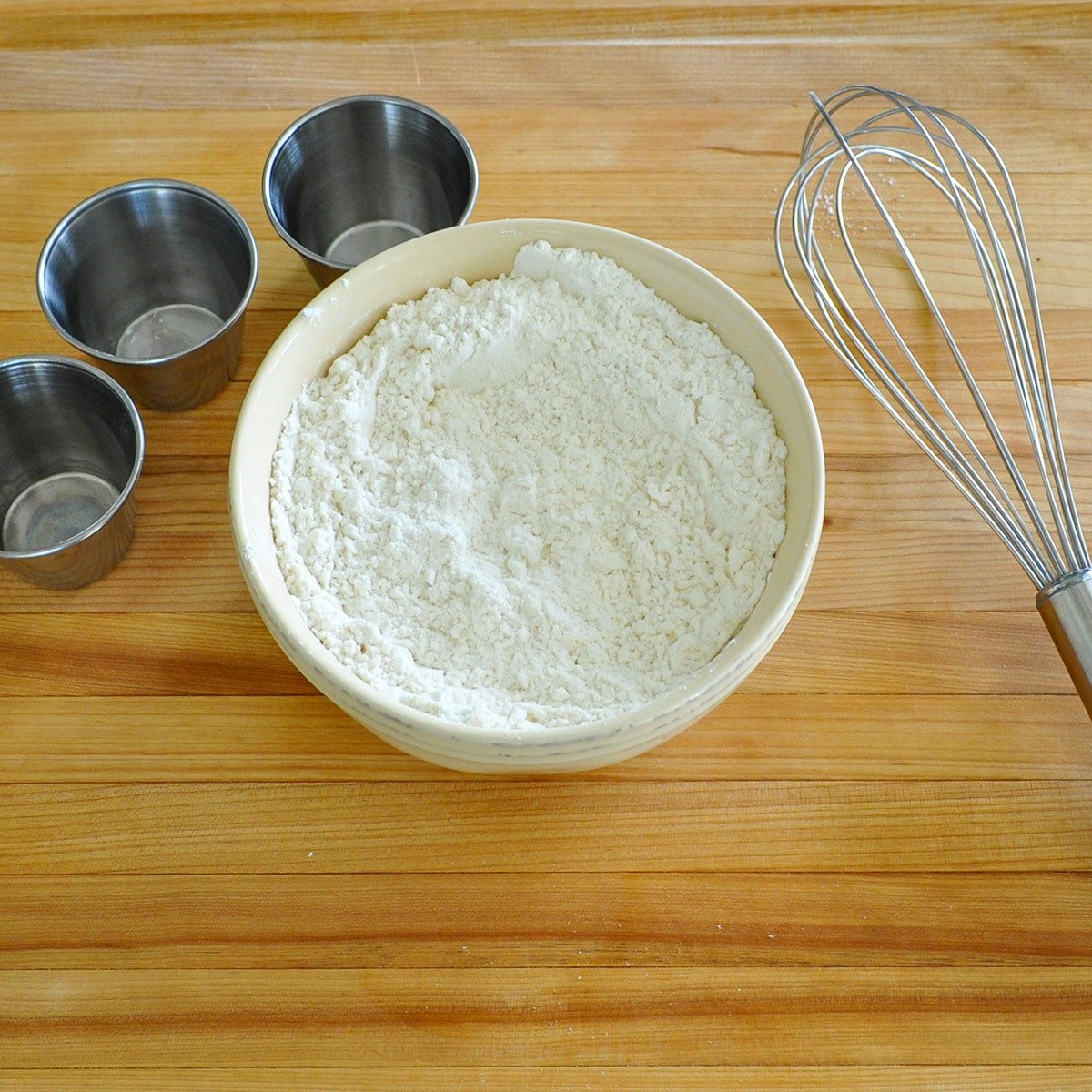 Flour mixed with baking powder, baking soda, and salt in a cream bowl next to a whisk