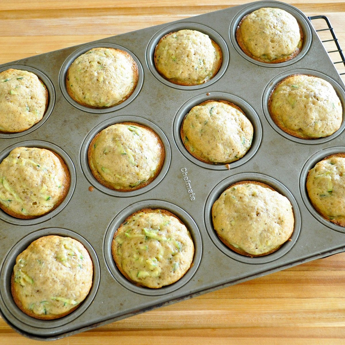 a muffin pan full of baked zucchini muffins
