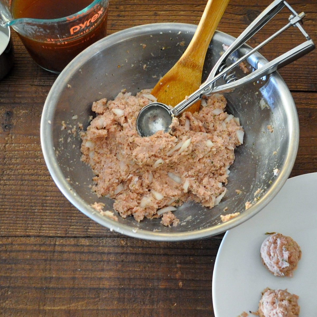 raw meatball mixture being made into meatballs using a cookie scoop