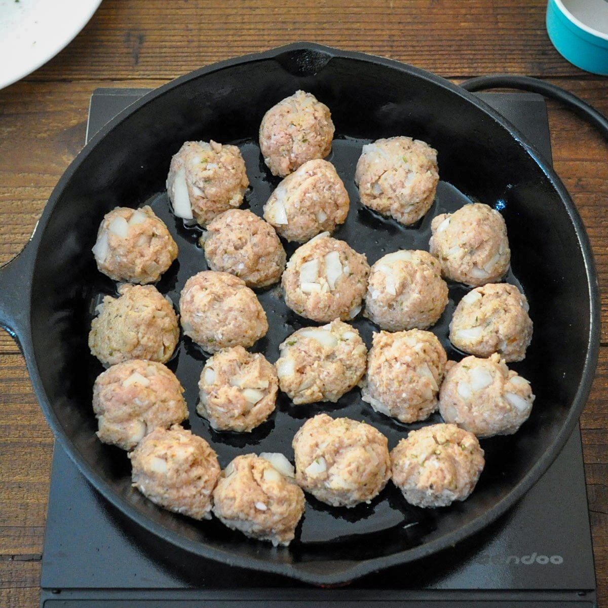 raw meatballs that were just placed in a cast iron skillet