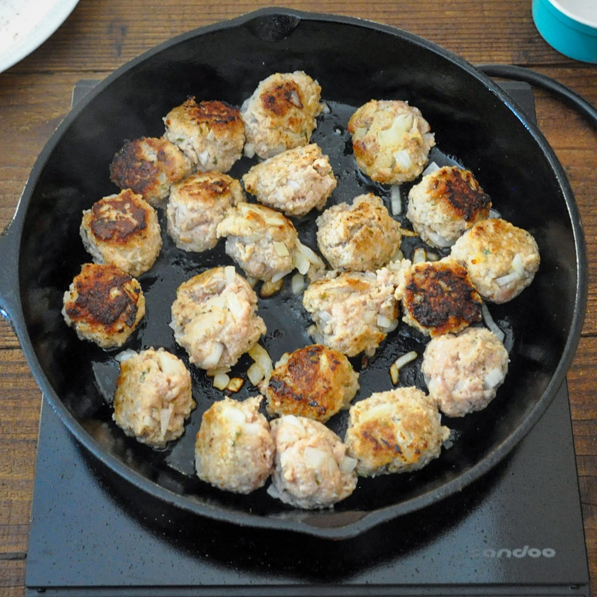 ground turkey meatballs cooking in a cast iron skillet