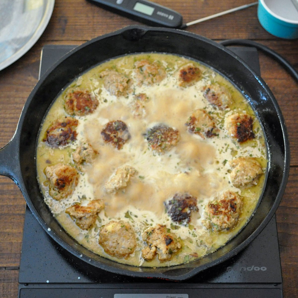 meatballs cooking in broth and cream in a cast iron skillet