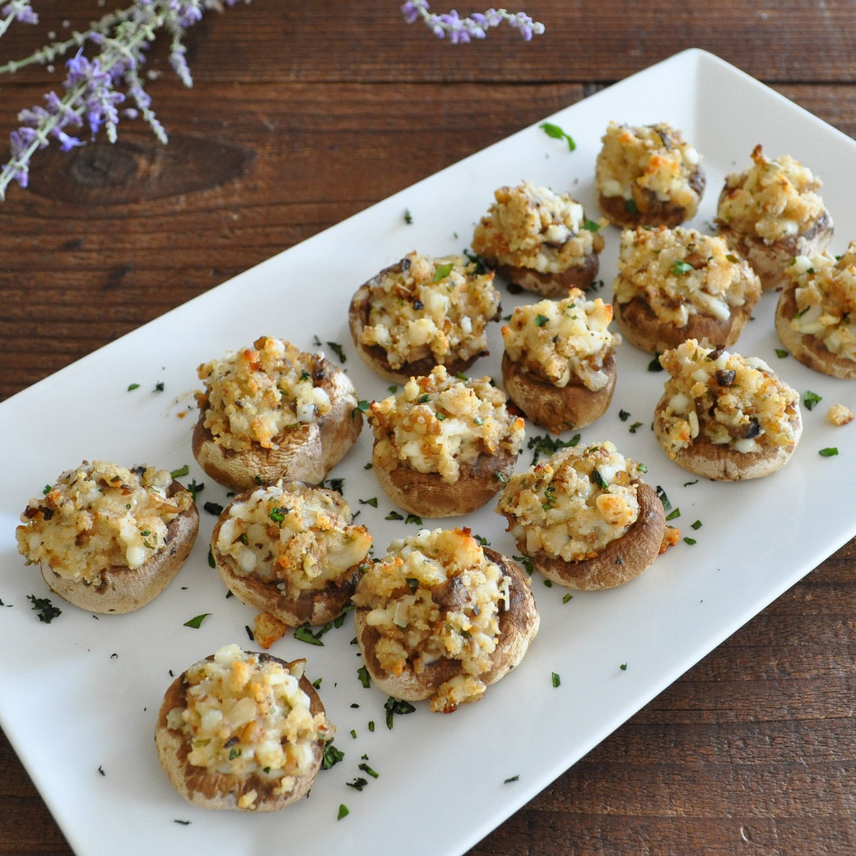 stuffed mushrooms on a white platter next to a bundle of lavendar