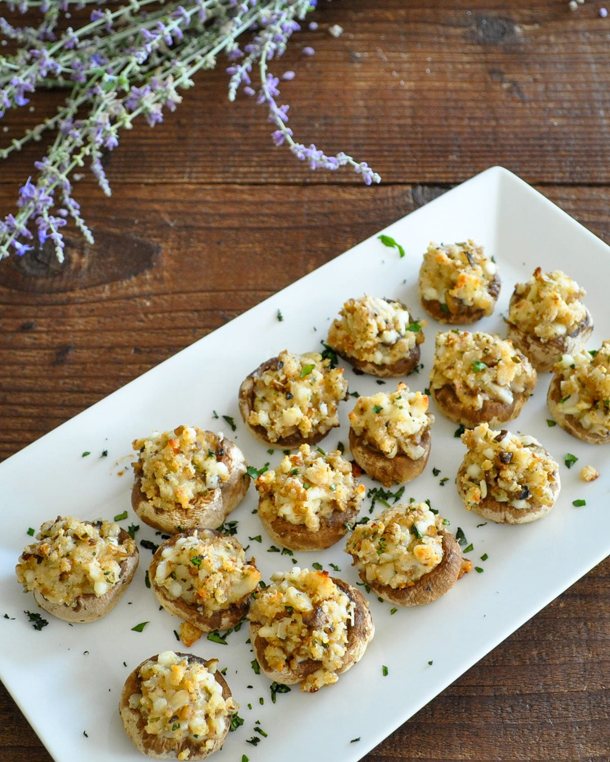 stuffed mushrooms on a white platter next to a bundle of lavender