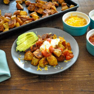 taco roasted potatoes on a gray plate with avocado sour cream cheese and salsa