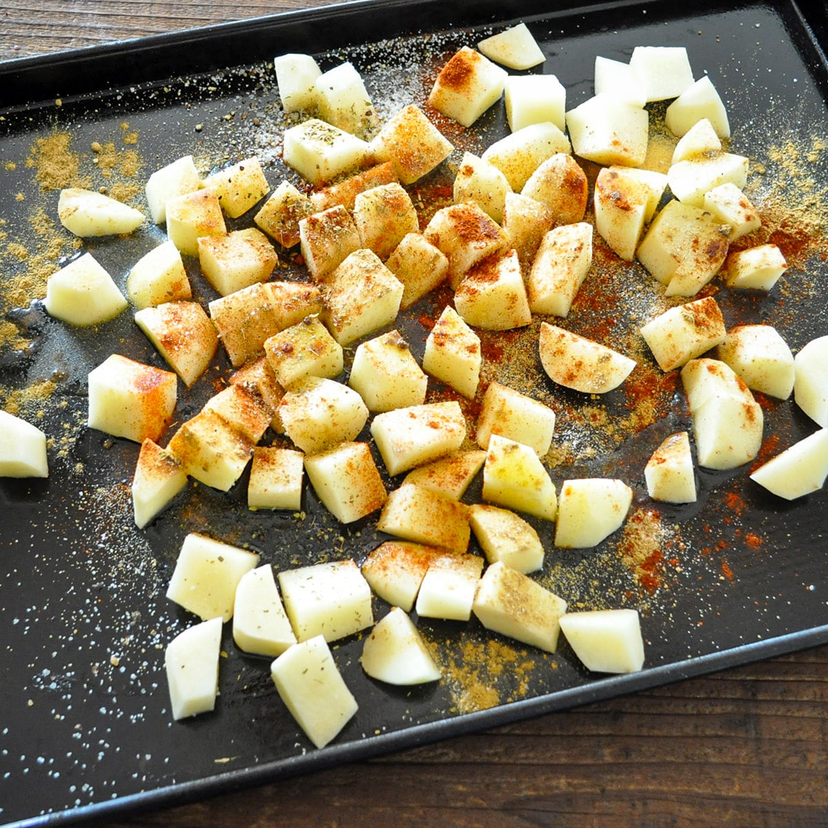 cubed potatoes with seasoning on a black cookie sheet