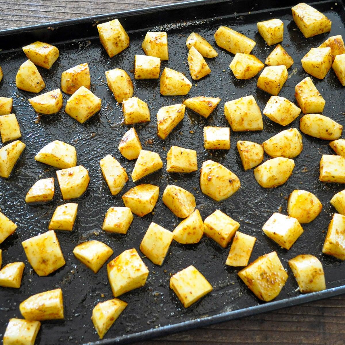 seasoned potatoes ready to bake on a black cookie sheet