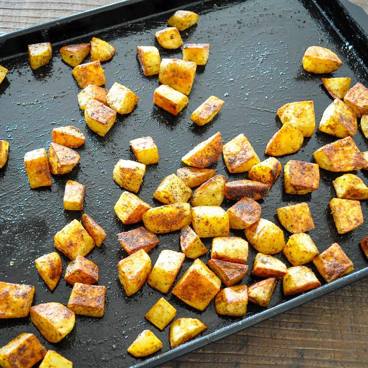 just baked seasoned roasted potatoes on a black baking sheet
