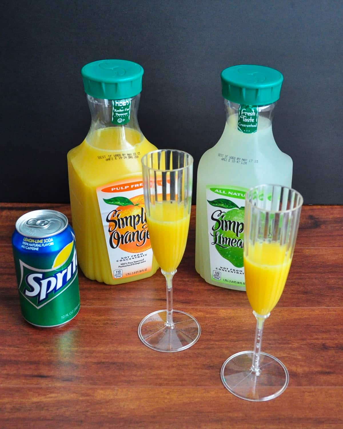 glasses half filled with orange juice sitting next to limeade and a can of sprite
