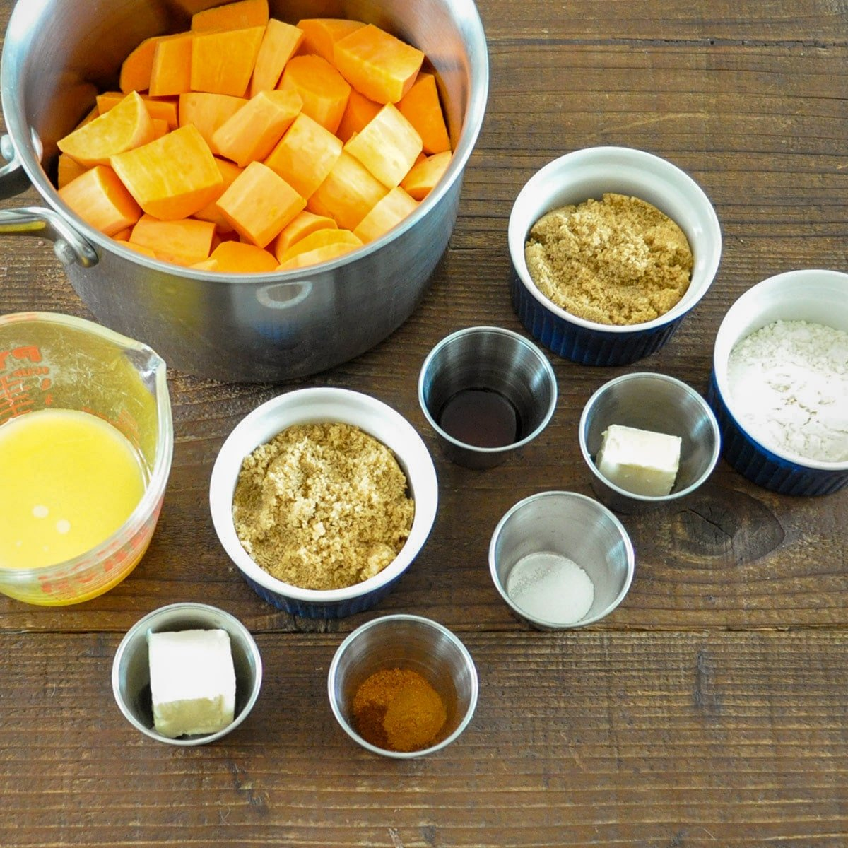 cut up sweet potatoes, orange juice, butter, flour, brown sugar, and spices measured for recipe