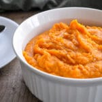 a white casserole bowl filled with mashed sweet potatoes